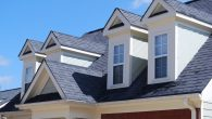 Top of house with a nicely laid out roof of asphalt shingles.