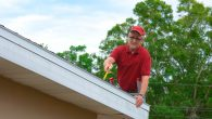 Man in red hat and shirt on top of ladder inspecting roof.