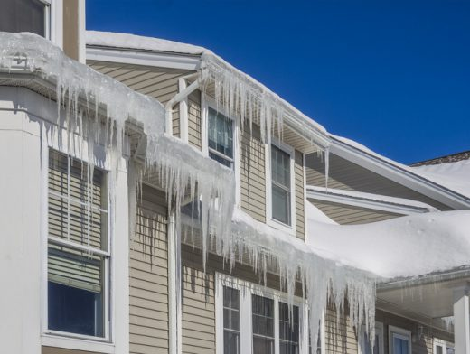 Ice dams and snow on roof and gutters after bitter cold in New England, USA