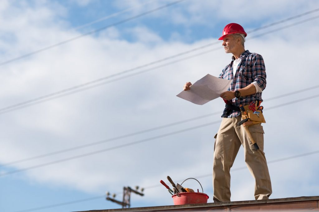 man standing on roof planning