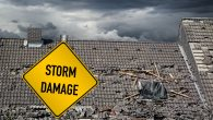 yellow damage warning sign in front of storm damaged roof of house