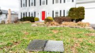 Front yard of house during day aftermath after storm roof tile shingle lying down on grass, damage closeup